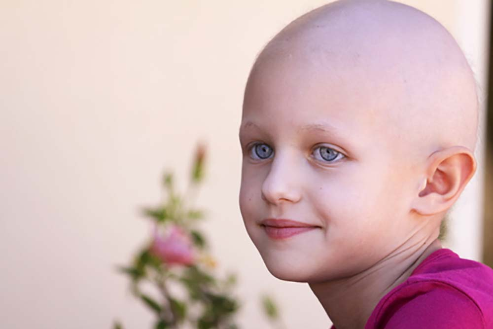 A child with a pink shirt and a bald head from chemo looks off to the left with a slight smile on their face. In the background a branch of a flowering bush is visible.